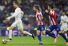 Real Madrid's Portuguese forward Cristiano Ronaldo runs with the ball ahead of Sporting Gijon's defender Lillo Castellano during the Spanish league football match Real Madrid CF vs Real Sporting de Gijon at the Santiago Bernabeu stadium in Madrid on November 26, 2016.