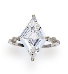 A diamond solitaire ring the lozenge-shaped diamond, weighing 3.65 carats, with single-cut diamond nine-stone shoulders; mounted in platinum
