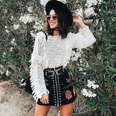 Pretty fringed blouse with cute print mini skirt and black hat.