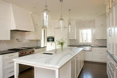 Three Corsica 1 Light Pendants hang over a long, narrow kitchen island topped with white marble with gray veining fitted with a small prep sink and gooseneck faucet.