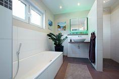 Helles Badezimmer mit Dusche und Badewanne.
