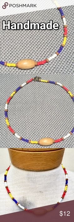 """Handmade unisex surfer necklace. Red, blue, wood This perfect surfer necklace features bold hand-formed seed beads of red, blue, white and yellow, interspersed with hand-cut wooden accents.  The colors will stand out on a bight day, and the short length is perfect for active lifestyles.   The length is adjustable, the antique bronze lobster-claw clasp can be fitted into any loop in the chain, making the length from 17-19.5"""". Wild Things Adornments Jewelry Necklaces"""