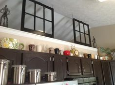 Old windows painted and used as a room divider above cabinets.