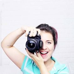 Menina segurando uma câmera fotográfica Canon T3i com blusa polo listrada de turquesa e branco em fundo branco, no quarto iluminado