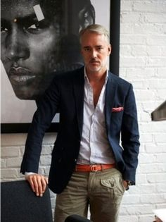 Michael Bastian wearing Navy Blazer, White Longsleeve Shirt, Orange Pocket Square, Orange Leather Belt, and Khaki Cargo Pants