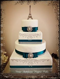 Fondant covered wedding cake with hand painted accents. Satin ribbon/bow and glitz broach.