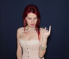 """Metal woman holding hands in the """"sign of horns"""" gesture. Isolated against blue background. #Woman #Portrait #Music #Metal #Horns #Gesture #hands #RedHair #RedHead #Female #Girl #BlueEyes #Fashion #Corset #Style #Beauty #Lips #Makeup #Cosmetics #Gothic"""