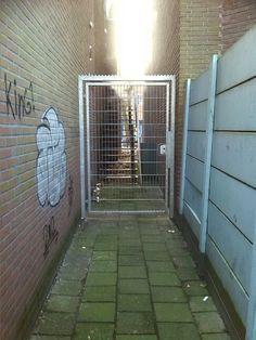 Poort door en dan naar de verzamel plek bij de voetbalkooi bij het andere gebouw