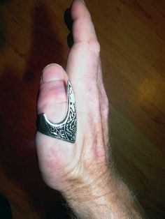 Mongolian Grip, use the middle thumb bone as aiming window, and the extension on this ring as a lever for heavy pound bows to how sting back. Index finger toward my target. Image 3 of 4.