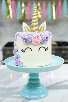 hier ist eine weiße einhorn torte mit einem weißen einhorn mit schwarzen augen und mit einer langen mähne mit pinken und lila rosen und einem goldenen langen horn einhorn torte anleitung