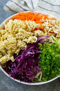 Shredded cabbage, broken up ramen noodles, shredded carrots, almonds and green onions in a bowl.