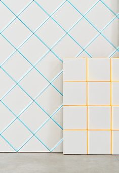 White square tiles with yellow or blue grout.