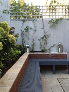 Built in garden bench seating painted in dark grey with contrasting light grey fence