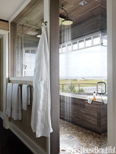 In a Shingle Style beach house decorated by Rob Southern, a six-by-nine-foot master bathroom shower has two Waterworks Easton Classic showerheads and stunning bay views. An interior window opens up the whole bathroom to sunlight and the views. Master Bathroom Shower, Bathroom Layout, Small Bathroom, Bathroom Storage, Master Bathrooms, Bathroom Ideas, Modern Bathrooms, Bathroom Organization, Bathroom Gray