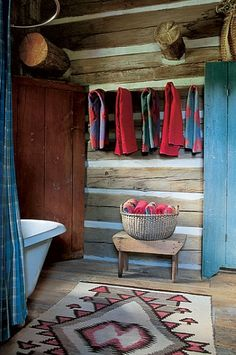 Elkmeadow Cabin A rebuilt clawfoot tub, a Shaker-style basket and a New Mexican Navajo rug are in the bath. Ralph Lauren Home multicolored towels; red Polo towels.