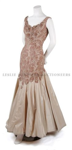 ~A Stitsworth Champagne Taffeta Gown, 1950s, with brown foliate overlay and appliques, trumpet skirt, fully lined. Labeled: Stitsworth Originals/Los Angeles~