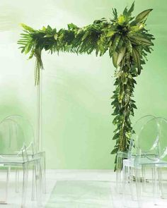 """Need proof that simple can be spectacular? Look up! This flower-free canopy requires only tropical foliage—ferns, philodendron, and jungle fronds, to be exact—to make a striking ceremony marker. Floral wire was used to wrap bunches of leaves around green-painted 4-by-4s. Asymmetry keeps it interesting, and rows of polycarbonate chairs allow for a clear view.Philippe Starck """"Victoria Ghost"""" chairs, rented from taylorcreativeinc.com"""