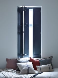 These full height solid shutters provide the perfect bedroom window dressing. The deep grey interior colour scheme and striped cushions give a nautical / coastal look to the room with contrasting colours.