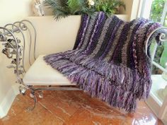 """My latest Crochet Addiction Creation. This one turned out huge as I miscalculated the pattern and needed to keep crocheting! haha. Done in greys and purples I used Homespun Edwardian for the dark stripes, a mixture of 3 strands of short eyelash and a chunky yarn for the light grey and a few rows of Pattons Pirouette scarf yarn for the contrasting stripes. I added a 9"""" fringe made up of about 8 different yarns (126 total fringe sets). Finished size-50"""" X 90"""" with fringe, Now onto the next…"""