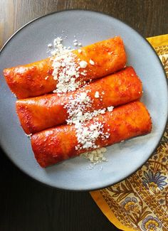 the tortilla, dipping in a red chile sauce, stuffed with queso fresco ...