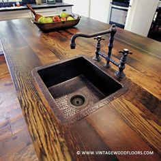 This reclaimed wood counter top gives this kitchen a rustic feel. | vintagewoodfloors.com