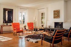 La deco vintage d'un mas provencal Devant l'âtre, deux fauteuils capitonnés de Guillerme et Chambron font face à deux fauteuils scandinaves vintage. La table, tout comme le lampadaire et le tableau au-dessus de la cheminée, a été trouvée aux puces. Les deux petites tables basses à plateau rouge sont de Roger Capron et le tableau, à gauche, de Jean-Louis Kolb.