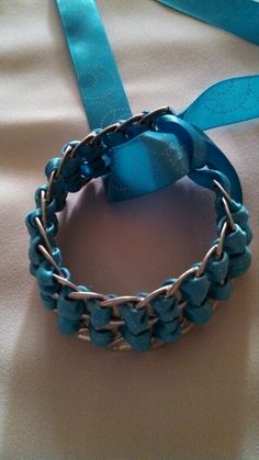 Soda pop tops and ribbon bracelet...takes between 17_19 pop tabs. Begin by scooting the first tab On to the middle if the ribbon with a loop to use later to tier back into..leave about 18 inches if ribbon down either side. Create a weave pattern...cheap and fun!