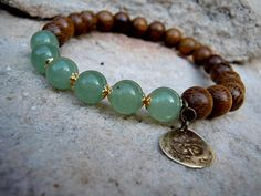 Combining green polished Aventurine beads and wooden mala beads with a handmade brass ohm charm. The elastic cord used for this bracelet is strong but plyable for a long lasting comfortable fit. Bead size : 8mm   < Please note that the wood beads used vary from medium to a dark shade of brown, that being said all beads are equally beautiful >  < As with most natural stones please allow variation in the shade of green, from lighter to a deeper green with the aventurine beads used for this…