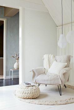 un joli fauteuil de lecture blanc avec tapis rond de salon