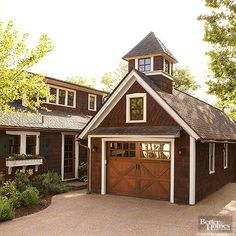 Plenty of modern-day garage upgrades do a good job recalling more traditional garage features. Here, the pretty wood door -- made to resemble closures on a barn or horse stable -- is actually a contemporary roll-up entry. Rich shake shingles set at an angle on the upper half of the garage and a pop-up window cupola also tie the structure to the home.