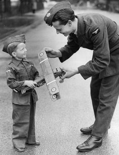 A boy offers his toy plane to an RAF man after a National request for scrap metal for the making of aircraft. 1940s