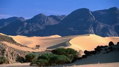 Dry river bed and sand dunes of Tazerzait with Air Mountains in background in Tenere part of Sahara desert near Agadez.