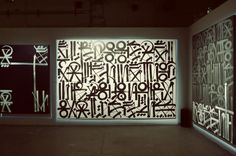Retna, the 31-year-old artist from Los Angeles. Retna, whose real name is Marquis Lewis, comes from a graffiti background. Over the past few years Retna has been known less for his graffiti pieces than a unique written language derived from various ancient scripts.    IT DRAWS ON EGYPTIAN HIEROGLYPHICS, AND MAYAN GLYPHS, AS WELL AS MEXICAN AND PRE-COLUMBIAN HERITAGE.