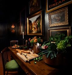 English country - table, opulent floral displays, gallery wall of gold-framed oils, British racing green, dark wood, dark walls