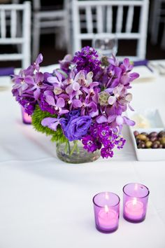 modern purple centerpiece mostly stock and other blooms with a hint of orchids