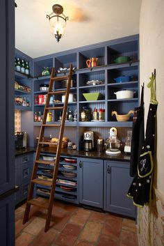 Amazing huge walk-in pantry. Love how there are cabinets on the bottom - provides more counter work space instead of just wall to wall shelves. the sliding ladder makes the space really functional for easily reaching the high shelves. super cute