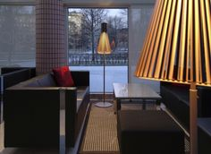 The Secto 4210 floor lamps with black shade spreading light at the cafe of  Tampere Hall in Finland. Photo by: Lasse Keltto. www.sectodesign.fi