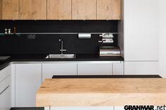 Blat kuchenny okładzina i wyspa w tej kuchni zrobione są  z konglomeratu kwarcowego Nero w obróbce powierzchni antykowanej