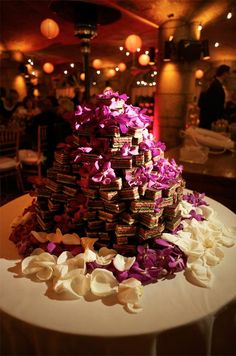 """The couple's wedding """"cake"""" is actually a tower of layered cookies decorated   with orchids and rose petals."""