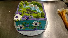 An eight inch square cake with fondant ducks and a feminine garden scene.