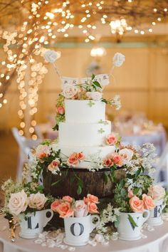 Andy Land (a nickname given to the couple by their friends) made the cake stand themselves. Unstructured gatherings of roses and greenery in lettered mugs finished the dessert display.