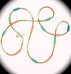 Long beaded necklace w/turquoise, pastel beads, & sterling heart toggle.