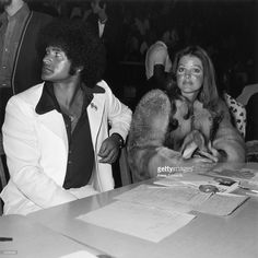 1975: American actor Priscilla Presley sits with her boyfriend, karate instructor Mike Stone, at a kung fu tournament at the Beverly Hills High School, California.