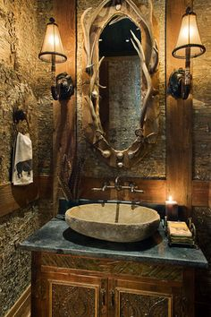 Luxury meets Rustic  Wild West in a bathroom that combines natural materials, like rough-cut stone, with antlers and some very nice hardware.