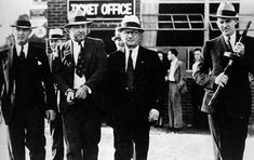 "FBI agents lead away American gangster George Kelly Barnes, better known as ""Machine Gun Kelly,"" who was wanted for the kidnapping of oil tycoon Charles F. Urschel in 1933."