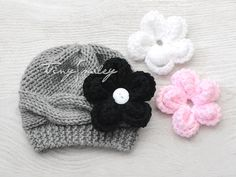 This listing is for one adorable gray knit baby beanie with 3 removable flowers (white, black and pink) for a baby girl. Sizes: 0 - 3 Mo.    Made with