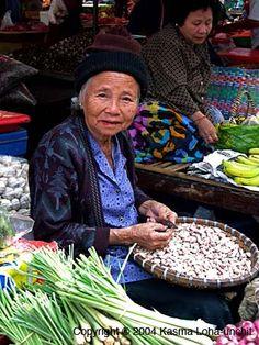 Elderly ethnic Vietnamese vendor at Nakhon Phanom's morning market.