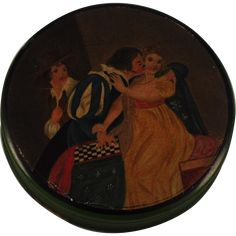 This  Georgian period papier mache snuff box is deocrated with a vividly hand painted indoor scene of a romantic man entangled with his love interest