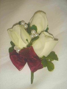 Rose Corsage - How To Make This is a simple rose corsage and quite easy to make. For added beauty, I've added pearls to it.  To make this, you'll need a wire cutter, corsage pin (safety pin), 3 cream roses (cut the stems to about an inch height), polycias or tea leaf, pearls in copper wire, floral tape, floral stem and ribbon.