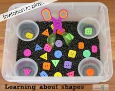 Learning about shapes in a sensory bin activity. You will need a small tub, 4 small containers, handy scoopers, shape buttons, and black aquarium rocks. The black aquarium rocks really bring out the colors in the shape buttons. Motor Activities, Sensory Activities, Classroom Activities, Preschool Activities, Preschool Shapes, Sensory Tubs, Sensory Boxes, Sensory Play, Sensory Diet